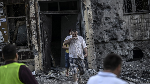 People come out from their houses after shelling in Donetsk