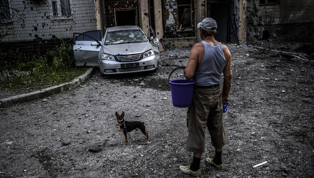 A man with his dog looks at a damaged area after shelling in Donetsk