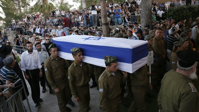 The coffin of a soldier draped in the Israeli flag is carried during his funeral