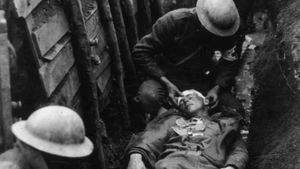 Red Cross workers in a trench tend to a wounded US soldier on a stretcher