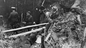 British Prime Minister David Lloyd George acknowledges cheers from British troops as he emerges from a captured German dug-out at Fricourt