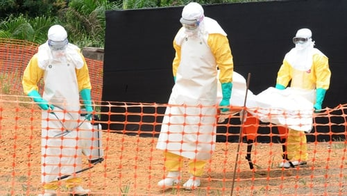 Doctors remove the body of a person killed by viral haemorrhagic fever in Guinea
