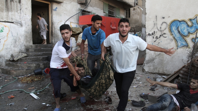 Palestinians carry a man who was wounded during an Israeli airstrike on a market place in the Shejaiya neighbourhood near Gaza City