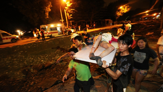 Residents carry a wounded person following a blast in the city of Kaohsiung in southern Taiwan