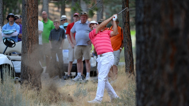 Padraig Harrington plays a shot out of the woods on the fifth hole