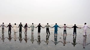 Local people make a hand chain as the Pakistani Navy rescue the bodies of the victims who drowned at the beach in Karachi