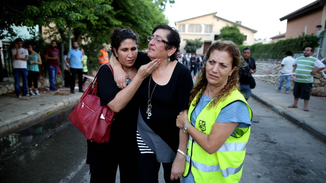 An Israeli women is helped from her home that was damaged after a rocket fired from Gaza landed in a residential neighbourhood in Kiryat Gat