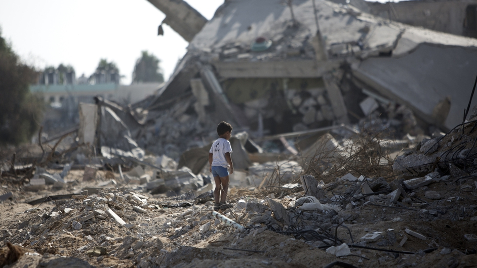 A boy stands alone in the rubble of his neighbourhood in Gaza City