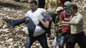Palestinian protesters carry a fellow demonstrator injured during clashes with Israeli security forces in a protest in the village of Kfar Qaddum in the West Bank