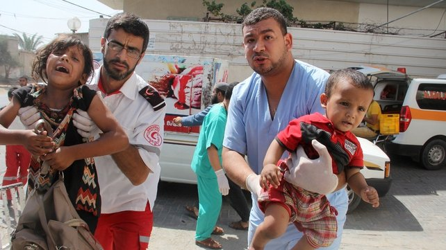 Injured children are carried into Al Najar hospital after Israeli air strikes in Rafah