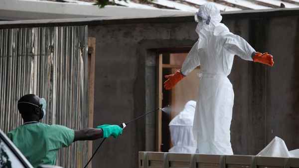 Liberian nurses are sprayed with disinfectant after preparing several bodies of victims of Ebola for burial