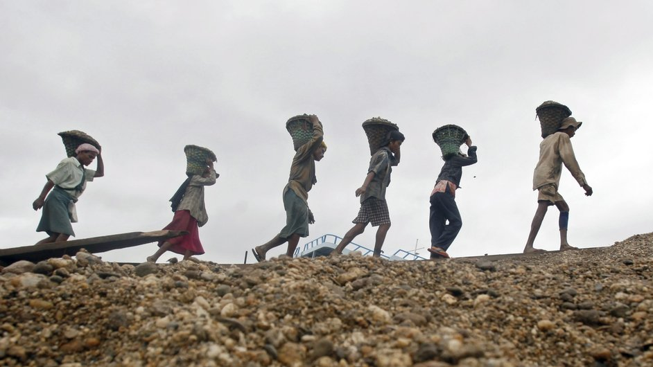 Burmese workers carry baskets loaded with gravel on their shoulders as they unload a boat at a jetty on the Yangon River