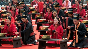 Chinese couples in traditional attire conduct a symbolic sharing of a meal during a group wedding ceremony of at least 66 couples coinciding with the Qixi Festival, or Double Seventh Festival, in Beijing
