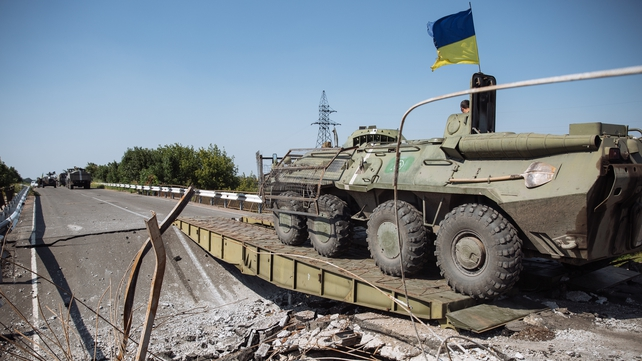 A Ukrainian Armoured Personnel Carrier (APC) crosses a destroyed bridge near Debalcevo