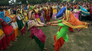 Indian women wearing traditional Punjabi attire sing folk songs dedicated to their husbands or fiances and perform the folk dance from Punjab 'Giddha' during an event to celebrate the Teej Festival in Amritsar