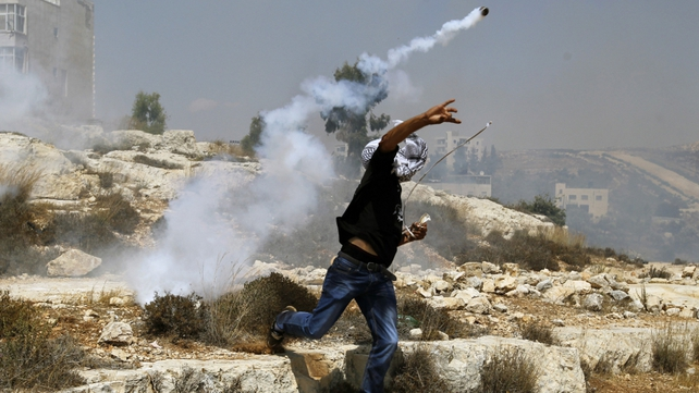 A Palestinian throws back a tear gas cannister towards Israeli security forces during clashes