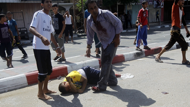 Palestinians assist a man injured in the strike