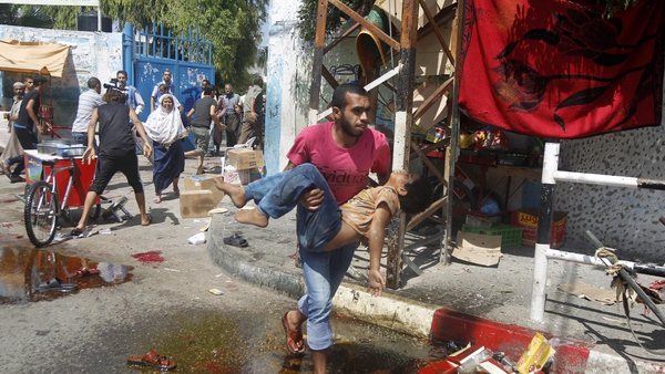 A Palestinian man carries an injured child following an Israeli military strike on a UN school in Rafah