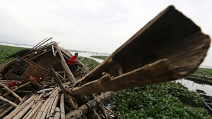 A Filipino resident emerges from a damaged home destroyed by a typhoon at a village in Taguig City, east of Manila, the Philippines