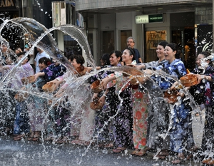 People dressed in 'yukatas', or cotton summer kimonos, splash water onto the ground along a street in the shopping area of Ginza in Tokyo. Hundreds of yukata-clad people participated in the annual summer event to cool off as temperatures soared over 35C
