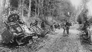 A lone soldier with a bicycle stands amid the remains of a German motor convoy which lines a country lane after an attack by French field guns in the battle of the Aisne in France