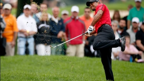 Tiger Woods grimaces as he plays out of the rough after aggravating his back injury