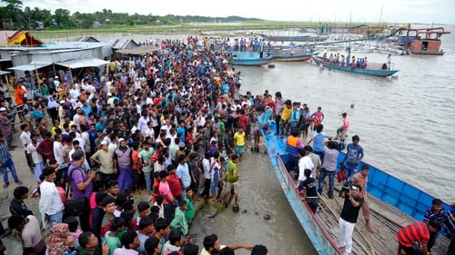 Local people and relatives gather at a beach after a ferry carrying  capsized in the Padma River