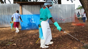 Liberian nurses spray disinfectant as a prevention against Ebola at a medical centre in the capital Monrovia