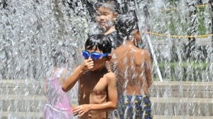 Children play in the fountain at a park in Tokyo