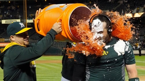 An Oakland Athletics player gets doused with Gatorade by a teammate after scoring a winning hit against the Tampa Bay Rays