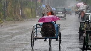 An Indian commuter sits under an umbrella on a cycle rickshaw during heavy rain in Kolkata