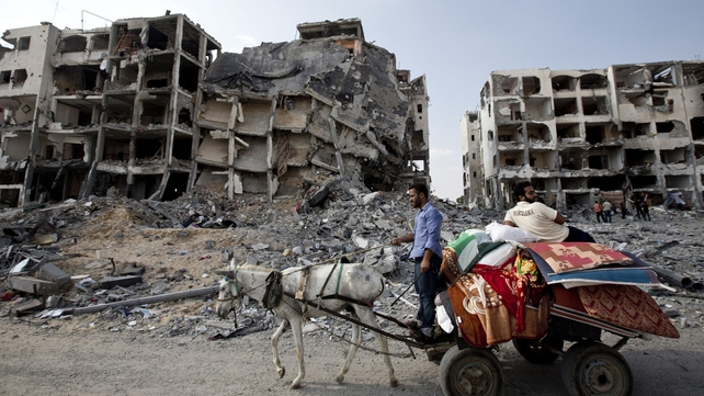 Palestinian men ride a donkey cart past destroyed buildings in northern Gaza