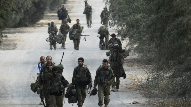 Israeli soldiers walk back to their bases after the truce