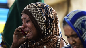 A woman whose brother is missing after a ferry capsized near Dhaka weeps as she speaks on the phone