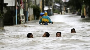 Filipino children wade in flood water in the town of Hermosa, Bataan