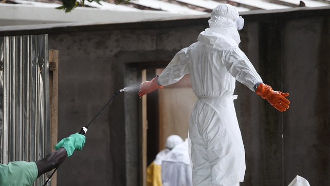 A Liberian nurse is sprayed with disinfectant after preparing victims of Ebola for burial