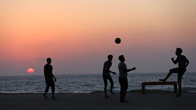Palestinian boys play football at the beach of Gaza City