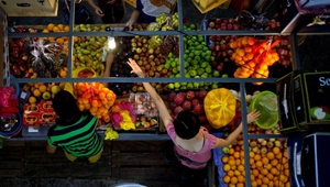 A Malaysian woman buys fruit at the Chow Kit wet market in downtown Kuala Lumpur.