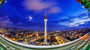 A fish eye lens view of evening clouds over the Berlin television tower from the viewing terrace of the Park Inn Hotel, Berlin, Germany.