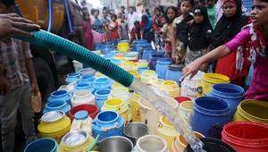 Indian locals line up with containers as they receive drinking water from the municipal water tanker that supplies drinking water in Calcutta