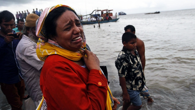Locals and relatives mourn near the Padma River where the ferry capsized