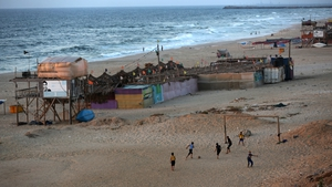 People play football on the beach in Gaza City