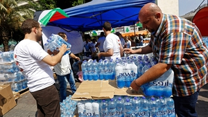 Palestinian volunteers in the West Bank city of Nablus prepare packs of water bottles to distribute to people in Gaza