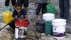 A Palestinian man and children fill containers with water from a broken main in Gaza City's al-Shejaea neighbourhood