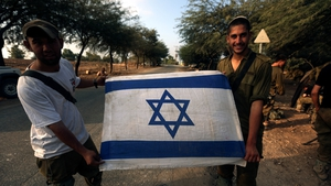 Israeli infantry soldiers hold an Israeli flag after they left Gaza