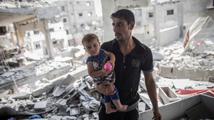 A Palestinian man holds his baby in the ruins of their destroyed home in Beit Hanoun