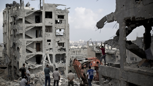 Palestinian men inspect the destruction in part of Gaza City's al-Tufah neighbourhood