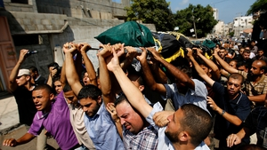 Mourners carry the body of the Al-Quds brigade's field commander Sha-aban Al-Dahdoh during his funeral in Gaza City