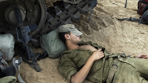 An Israeli soldier rests next to a tank at a new position a few kilometres from the Israel-Gaza border