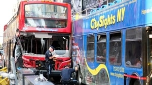 A police officer inspects two double-decker tour buses which collided in Times Square, New York